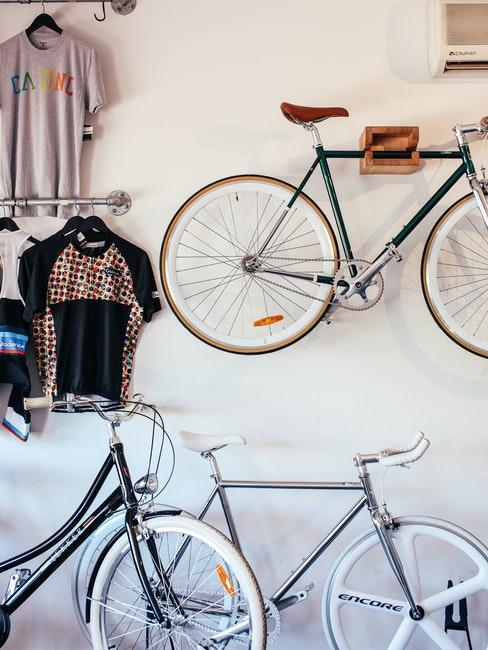 Fahrrad an einer Wandhalterung neben einer Kleiderstange, am Boden stehen zwei Fahrräder
