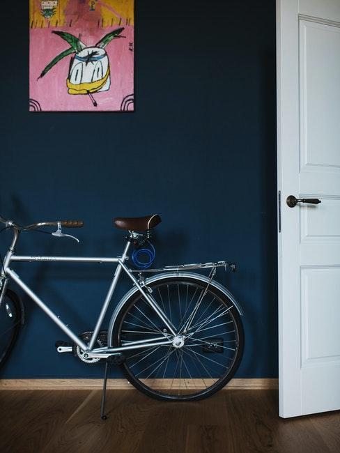 Fahrrad an einer dunkelblauen Wand mit einem Bild
