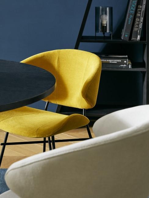 Gelber Stuhl vor dunkelblauer Wand