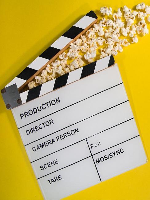 Regieklappe auf  gelben Hintergrund mit Popcorn
