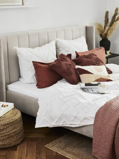 Taupefarbenes Bett mit rötlichen Kissen