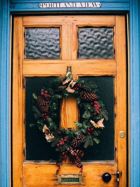Kranz mit Weihnachtsdeko an einer Haustür