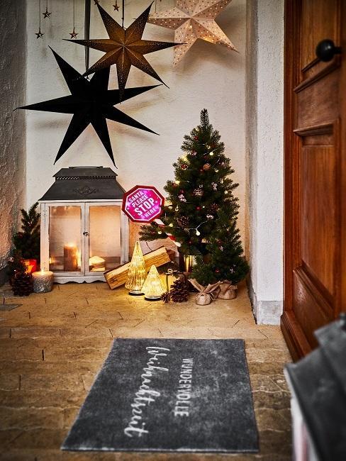 Weihnachtsbaum mit Sternen und Windlicht vor der Haustür