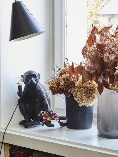 getrocknete Hortensien und andere Herbstblumen in Vasen am Fenster mit Affenlampe