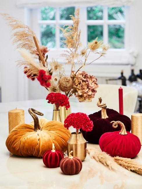getrocknete Herbstblumen in Vasen mit Dekokürbissen und Kerzen