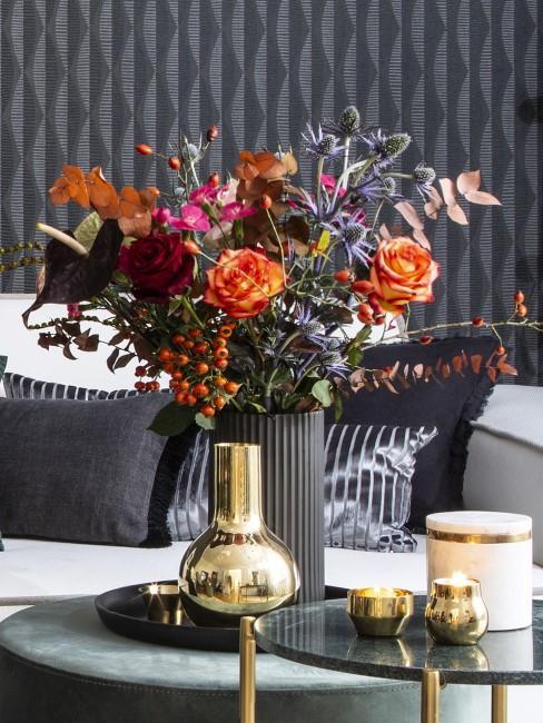 Herbstblumen in Vase auf Beistelltisch mit Kerzen und Vase