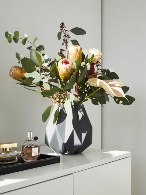 Herbstblumen in Vase auf Kommode