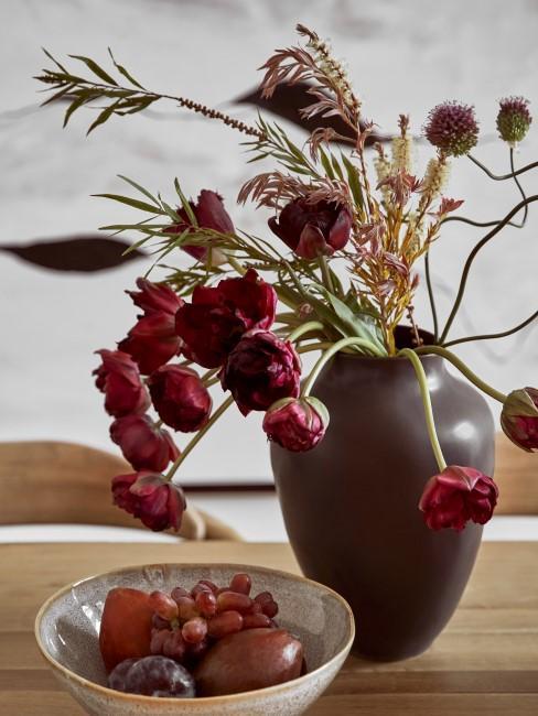 roter Herbstblumenstrauß in Vase auf dem Esstisch