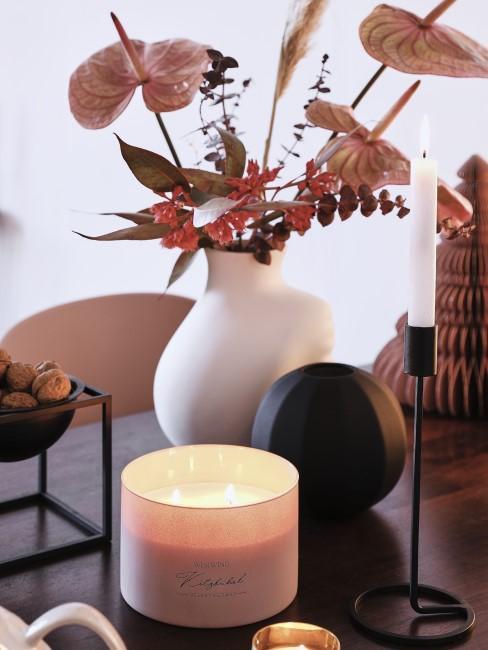 Herbstblumen in Rotnuancen mit Kerze und Nüssen dekoriert