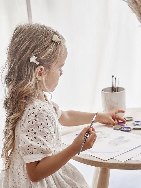 Mädchen malt auf einem Papier