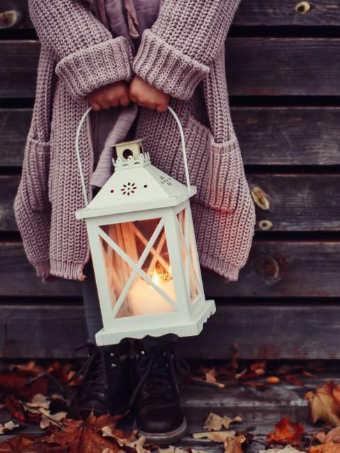 Frau mit Laterne als Herbstdeko vor dem Hauseingang