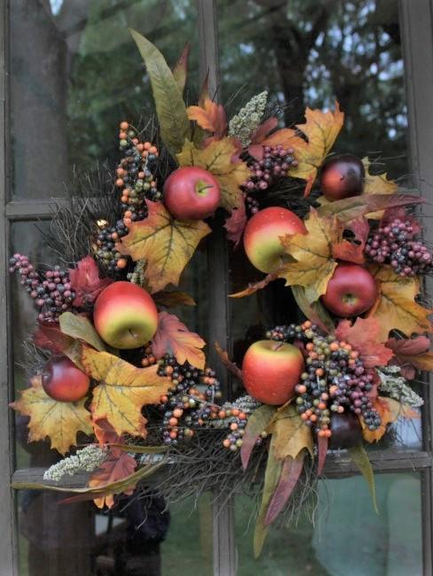 Herbstkranz mit Blättern, Beeren und Apfeln an der Tür