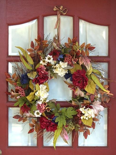 Herbstkranz mit Blumen und Blättern an der Tür