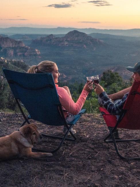 Paar genießt Sonnenuntergang beim Camping mit Hund