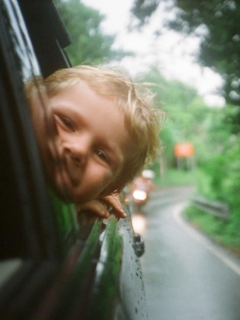 Kind steckt Kopf aus dem Autofenster
