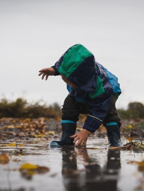 Kind in Regenkleidung spielt in Pfütze