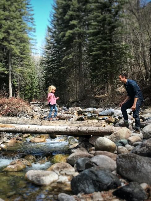 Mädchen balanciert über Baumstamm am Fluss