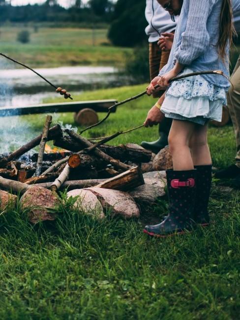 Mädchen mit Gummistiefeln am Lagerfeuer