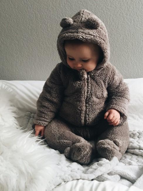 Baby in Kuschelanzug mit vielen Decken und Fell