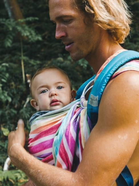 Papa mit Baby im Tragetuch beim Camping mit Baby