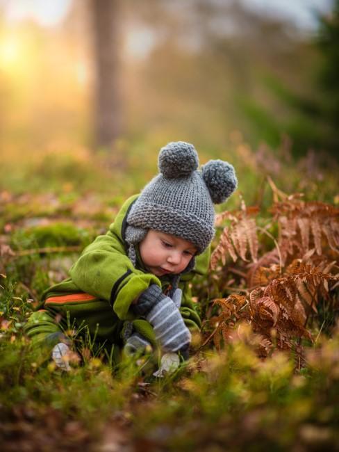 Kleinkind in wetterfester Kleidung in der Natur beim Camping mit Baby