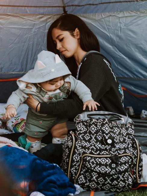 Mama mit Baby und Rucksack im Zelt beim Camping mit Baby