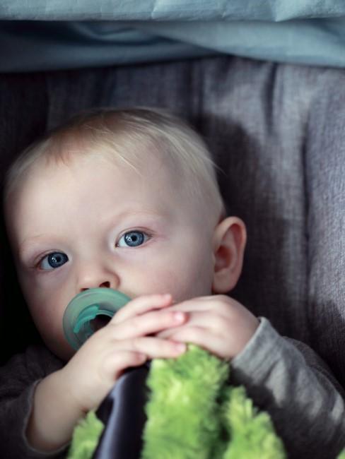 Baby mit Schnuller in der Babyschale