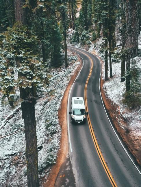Wohnmobil bei Fahrt durch den winterlichen Wald