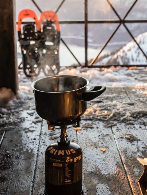 Schneeschuhe und Gaskocher mit Topf beim Wintercamping