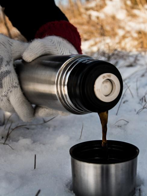Thermoskanne mit Kaffee beim Wintercamping