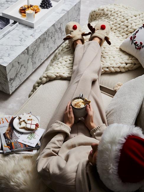 Frau in gemütlicher Kleidung auf einem Sofa