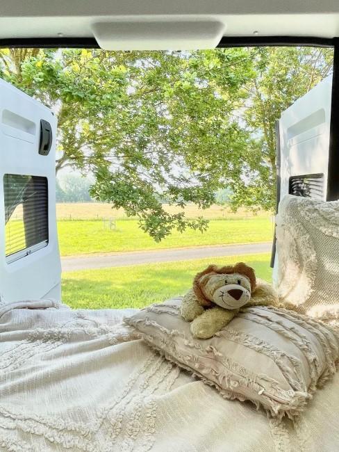 Blick aus dem Camper mit Decke und Kissen im Boho-Stlye