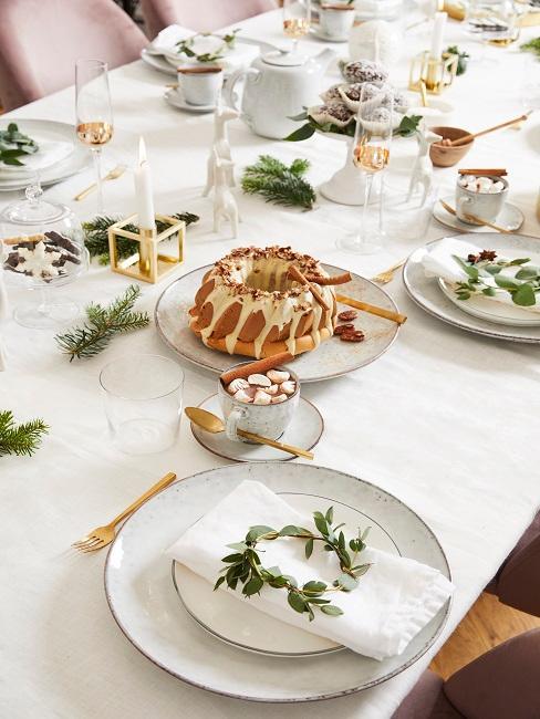 Gedeckter Tisch mit Weihnachtsdeko und einem Kuchen