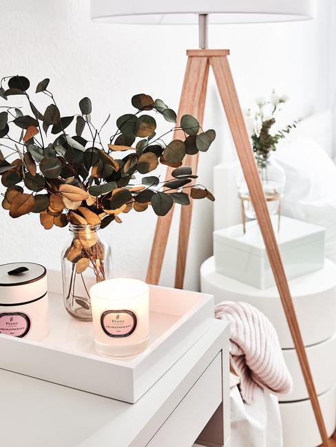 Dormitorio blanco decorado con plantas y velas