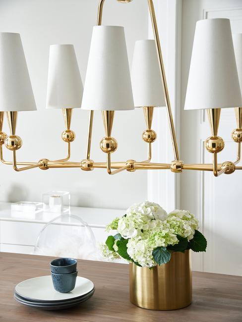 Lámpara dorada y jarrón de flores dorado