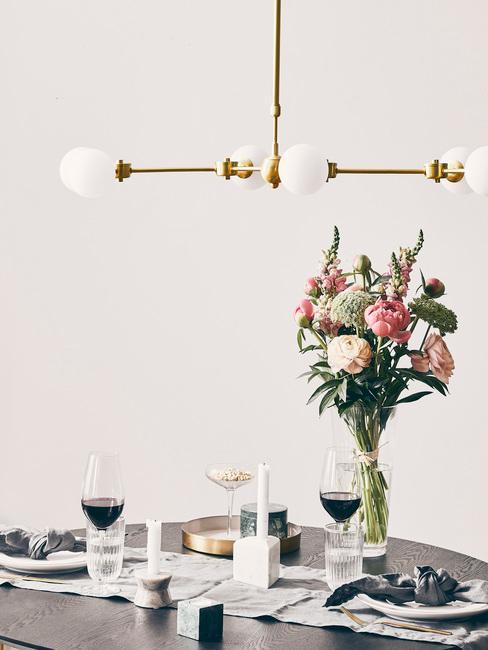 Mesa gris con copas de vino tinto y jarrón con flores