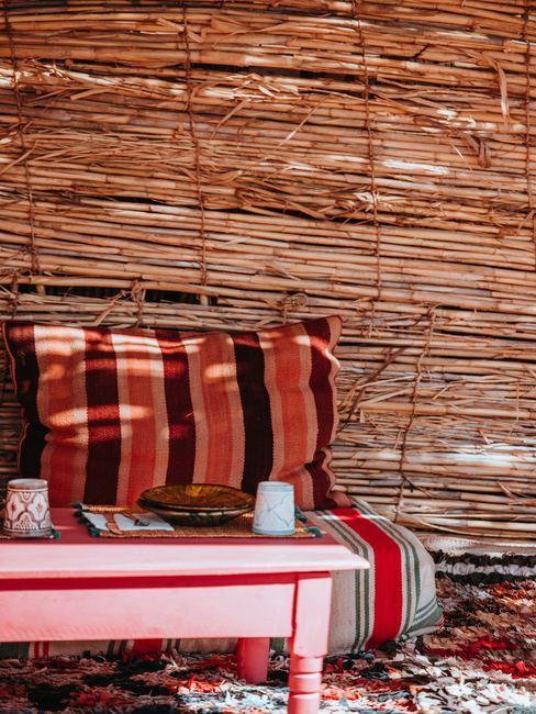 Platos de bambú sobre mesa roja con pared de bambú