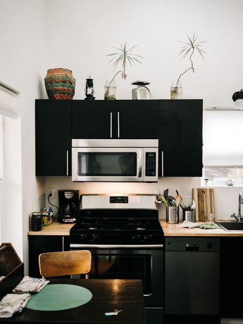 Cocina pequeña en tonos negros y blancos con horno de fondo
