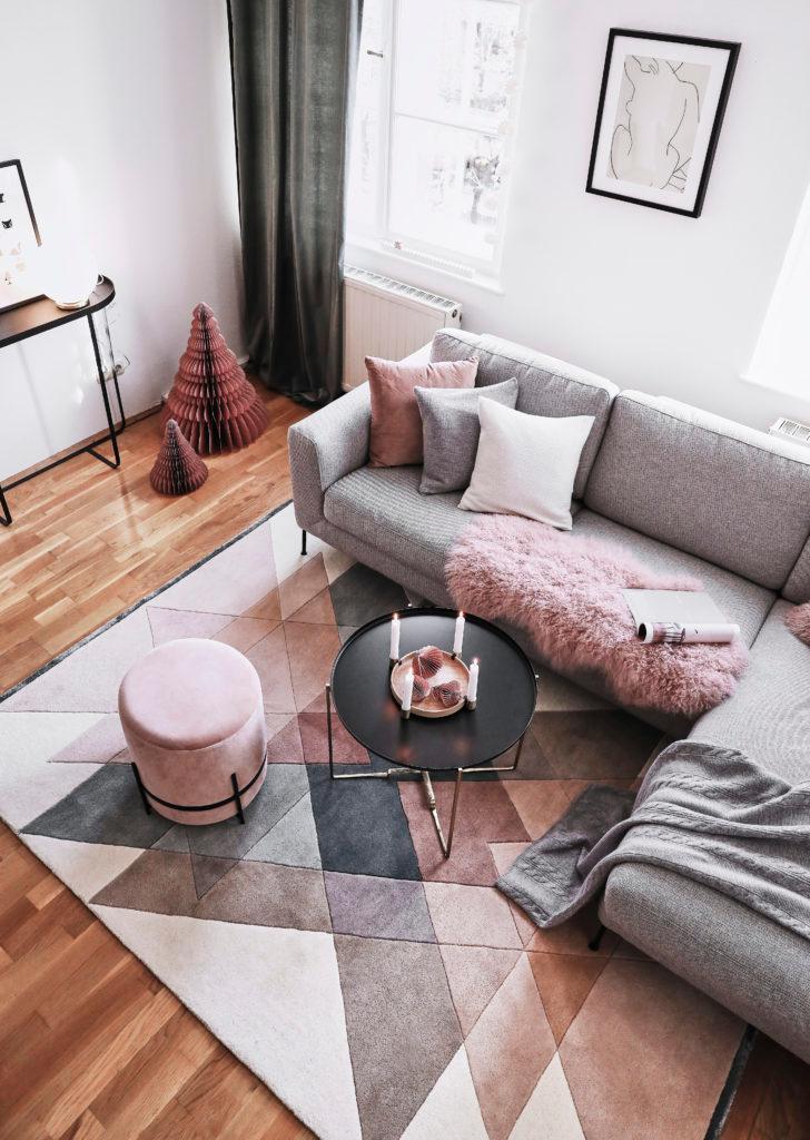 salón al estilo escandinavo con un sofá gris, puf rosa y alfombra con estampado geométrico