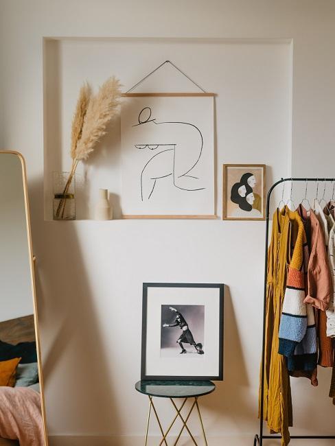 cuadros y fotos en una habitación pequeña, una burra con ropa y un espejo