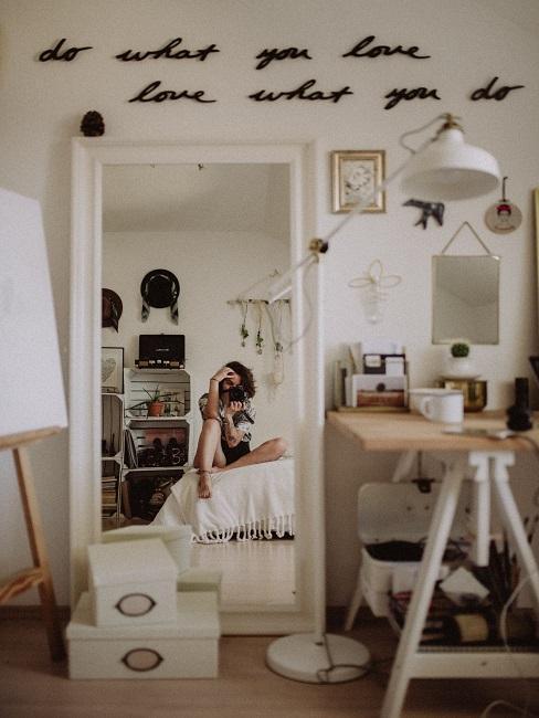 dormitorio pequeño decorado en blanco, con un espejo grande y con inscripción sobre la pared