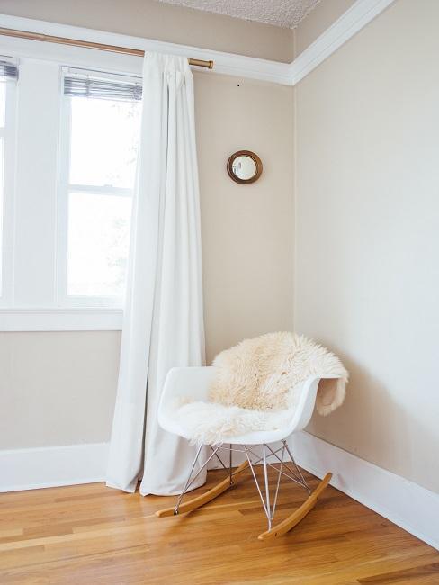 dormitorio blanco con una mecedora blanca con piel de oveja blanca