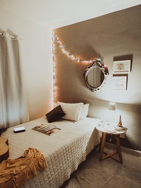 dormitorio en colores blanco y beige, con una guirnalda de luces