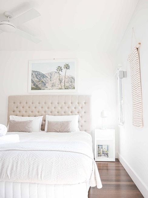 cama grande en color beige y con ropa de cama blanca