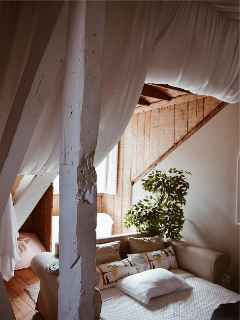 sofá cama beige en una casa de madera con persianas blancas