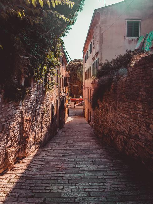 Callejuela estrecha rodeada de muros de ladrillo marrón sobre adoquines
