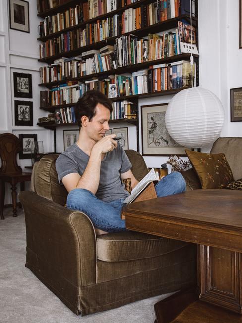 Chico sentado en una butaca antigua de peil color marrón delante de una mesa de madera marrón delante de una gran estantería llena de libros