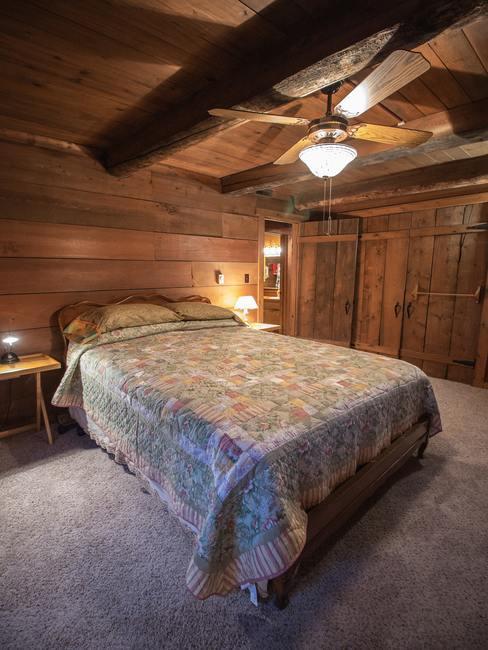 Dormitorio de estilo campestre con techos de madera de color marrón