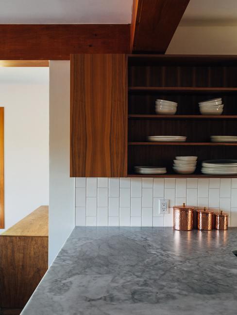 Encimera grande en cocina y estantería de madera con platos llanos y soperos