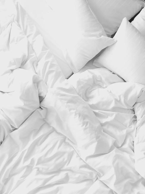 Cama deshecha con edredón blanco y cojín blanco, ambos sin fundas